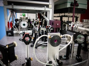 """Le réseau laser. Le faisceau de faible puissance passe à travers des optiques dont certaines en Saphir-titane (en rouge) et est """"pompé"""" par des faisceaux secondaires (en face en vert)."""